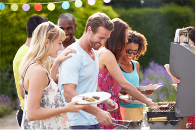 Adults enjoying a backyard barbeque party in the summer.